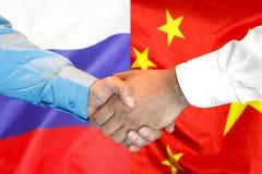 Handskakning på Kina och Ryssland flaggabakgrund royaltyfri bild