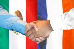 Handskakning på Mexico och Frankrike flaggabakgrund royaltyfria foton