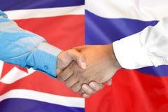 Handskakning på Nordkorea och Ryssland flaggabakgrund fotografering för bildbyråer