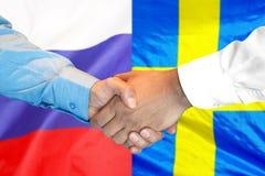 Handskakning på Sverige och Ryssland flaggabakgrund royaltyfri foto