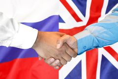 Handskakning på UK- och Ryssland flaggabakgrund royaltyfria bilder