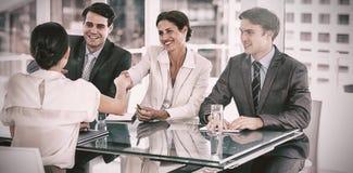 Handskakning som förseglar ett avtal efter ett jobbrekryteringmöte arkivfoto