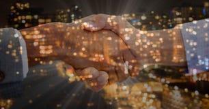 handskakningförgrund Överlappning med staden på natten Royaltyfri Foto