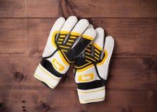 Handskar av fotbollmålvakten på trätabellen Arkivfoton