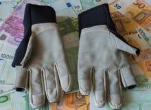 Handskar för att segla mot bakgrunden av eurosedlar Arkivfoto