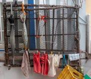 Handskar och paraplyer för fiskaren som hänger vid ingreppet på väggen royaltyfri foto
