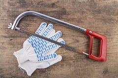 Handskar och såg på tabellen Fotografering för Bildbyråer