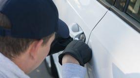 Handskerånaren bryter lagen, hackar låset på bilen för att få inom royaltyfri bild