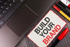 Handskrifttextbyggande ditt märke Begreppsbetydelsen skapar din egen logosloganmodell som annonserar att marknadsföra för E som ä royaltyfri fotografi