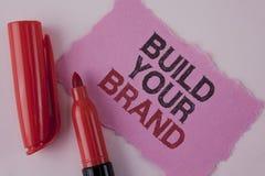 Handskrifttextbyggande ditt märke Begreppsbetydelsen skapar din egen logosloganmodell som annonserar att marknadsföra för E som ä royaltyfria foton