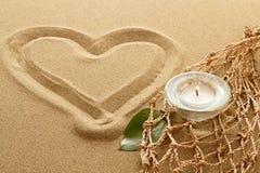 Handskriven hjärta på sanden med tände stearinljus Arkivbild
