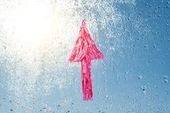 Handskriven röd pil på regnigt fönster Bakgrundsdroppe av vatten på exponeringsglaset, blå himmel, sol Arkivbild