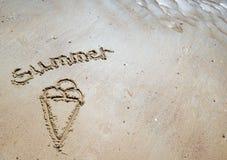 Handskriven sommar i sanden av stranden med en älskvärd hjärta Fotografering för Bildbyråer