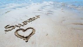 Handskriven sommar i sanden av stranden med en älskvärd hjärta royaltyfria bilder