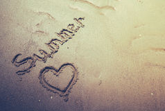 Handskriven sommar i sanden av stranden med en älskvärd hjärta royaltyfri bild
