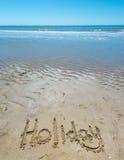 Handskriven sommar i sanden av stranden med en älskvärd hjärta arkivfoto