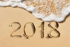 Handskrivet nytt år 2018 på sanden Arkivfoton