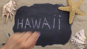 Handskrivet ord HAWAII som är skriftlig i krita, bland snäckskal och stjärnor Top beskådar stock video