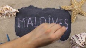 Handskrivet ord MALDIVERNA som är skriftlig i krita, bland snäckskal och stjärnor Top beskådar arkivfilmer