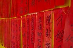 Handskrivna kinesiska calligraphic charactors på röda etiketter Arkivfoto