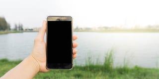 Handsmartphone im Park Lizenzfreie Stockbilder