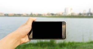 Handsmartphone im Park Stockbild