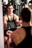 Handsom在健身健身房的年轻人锻炼 图库摄影