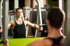 Handsom在健身健身房的年轻人锻炼 免版税图库摄影