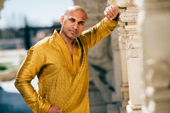 Handsom Indian Man in Gold Kurta at the Temple. The handsome Indian man wears a gold kurta and posed at a temple Stock Photo