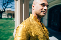 Handsom Indian Man in Gold Kurta at the Temple. The handsome Indian man wears a gold kurta and posed at a temple Royalty Free Stock Photography