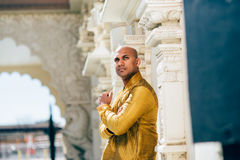 Handsom Indian Man in Gold Kurta at the Temple. The handsome Indian man wears a gold kurta and posed at a temple Royalty Free Stock Image