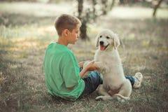 Handsom Szene des Retrieverwelpen reizendes jugendlich Junge, der Sommerzeitferien mit Labrador-Welpen des Elfenbeins des besten  lizenzfreie stockfotos