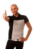 Handsom ung man som gör en gest framgång med tummen som upp över isoleras Arkivbild