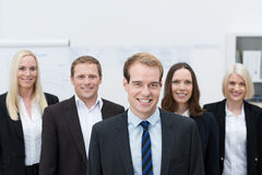 Handsom young manager with a happy team behind him. Handsom young Caucasian manager smiling with a happy team made of three women and a man, behind him Stock Photography