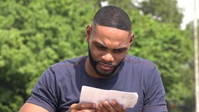 Unhappy Black Man Reading A Document