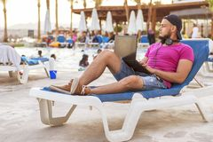 Handsome adult caucasian man with black beard in jeans shorts an. D purple t-shirt and a cap laying at tropical resort pool on his vacation, listen music in Stock Photography