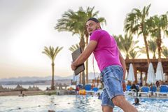 Handsome adult caucasian man with black beard in jeans shorts an. D purple t-shirt and a cap running at tropical resort pool on his vacation, listen music in Royalty Free Stock Photos