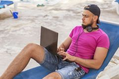 Handsome adult caucasian man with black beard in jeans shorts an. D purple t-shirt and a cap laying at tropical resort pool on his vacation, listen music in Royalty Free Stock Image