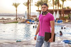 Handsome adult caucasian man with black beard in jeans shorts an. D purple t-shirt and a cap standing at tropical resort pool on his vacation, listen music in Royalty Free Stock Photo