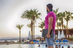 Handsome adult caucasian man with black beard in jeans shorts an. D purple t-shirt and a cap standing at tropical resort pool on his vacation, listen music in Royalty Free Stock Images