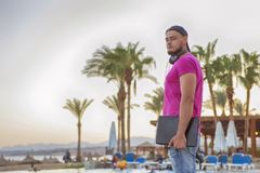 Handsome adult caucasian man with black beard in jeans shorts an. D purple t-shirt and a cap standing at tropical resort pool on his vacation, listen music in Royalty Free Stock Image
