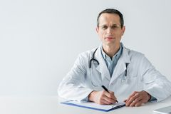 Handsome adult doctor sitting at workplace and writing diagnosis in clipboard. Isolated on white stock photos