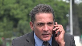 Excited businessman using cell phone. A handsome adult hispanic man stock footage