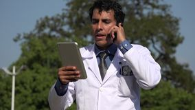 Happy hispanic doctor diagnosis using tablet. A handsome adult hispanic man stock footage