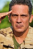 Male Soldier Saluting. A handsome adult hispanic man Stock Image