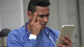 Hispanic Male Surgeon Thinking With Tablet. A handsome adult hispanic man stock video footage