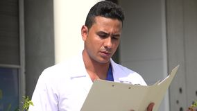 Serious Hispanic Male Doctor Reading. A handsome adult hispanic man stock video footage