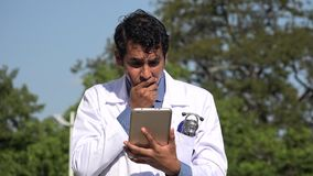 Stressed hispanic doctor using tablet. A handsome adult hispanic man stock video footage