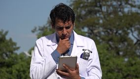 Worried hispanic doctor using tablet. A handsome adult hispanic man stock footage
