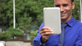 Young Hispanic Business Man Filming Video Using Tablet